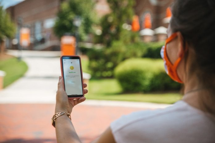 woman looks at phone displaying campus clear app