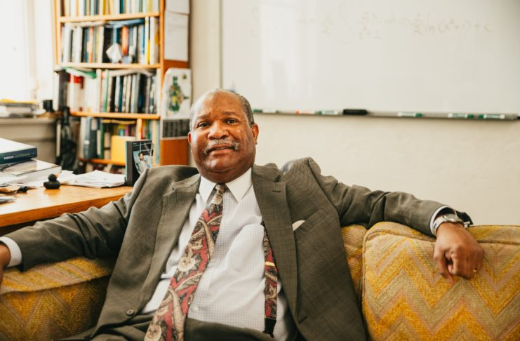 Dr. Kedrick Hartfield sits on a couch in his office
