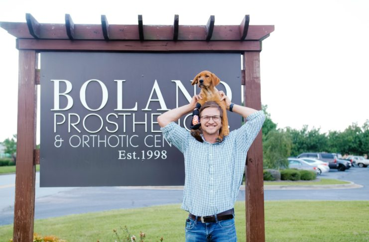 a man holds a dog on his shoulders in front of a sign for boland prosthetics and orthotic center